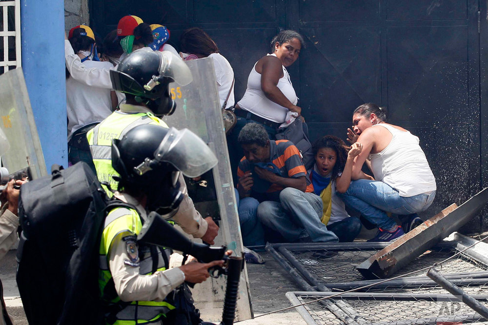 Anti-government demonstrators take cover from advancing Bolivarian Police officers during protests in Caracas, Venezuela, Wednesday, April 19, 2017. Opponents of President Nicolas Maduro called on Venezuelans to take to the streets and march against the embattled socialist leader. (AP Photo/Ariana Cubillos)