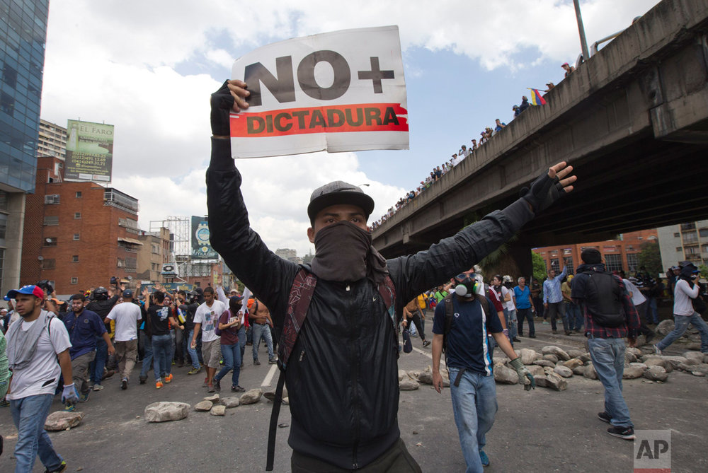 "A demonstrator holds up a sign that reads in Spanish read ""No more dictatorship"" during a protest in Caracas, Venezuela, Thursday, April 6, 2017. The South American country has seen near-daily protests since the Supreme Court issued a ruling nullifying congress last week. The court pulled that decision back after it came under heavy criticism, but opposition leaders said the attempt to invalidate a branch of power revealed the administration's true dictatorial nature. (AP Photo/Ariana Cubillos)"