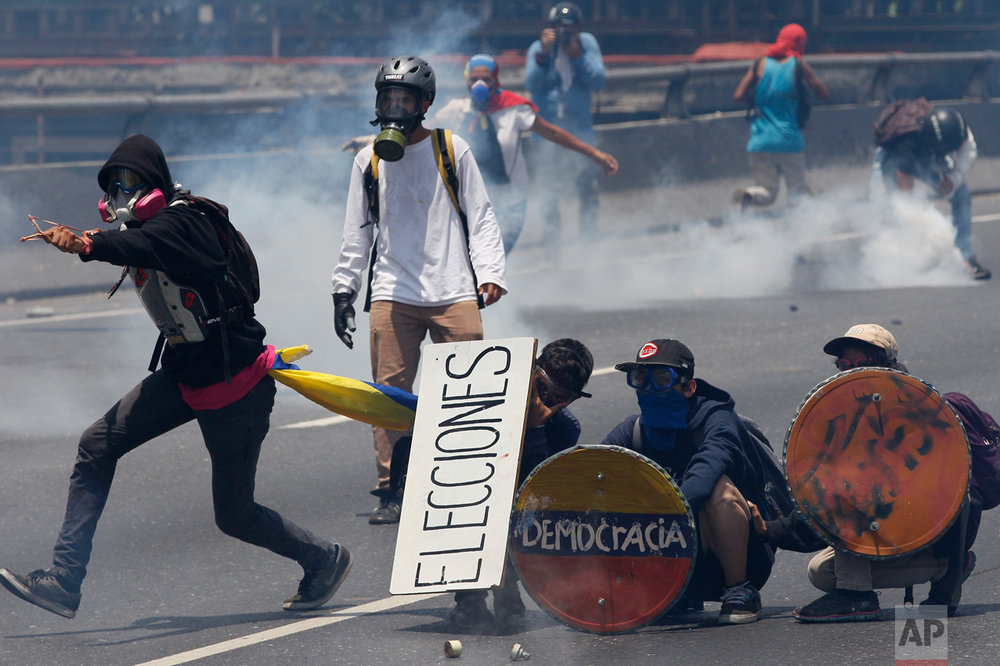 Opponents of President Nicolas Maduro take cover behind homemade shields during clashes with security forces blocking them from marching to the Ombudsman's office in downtown Caracas, Venezuela, Wednesday, April 26, 2017. Hundreds of thousands of Venezuelans have flooded the streets over the last month to demand an end to Maduro's presidency. (AP Photo/Ariana Cubillos)