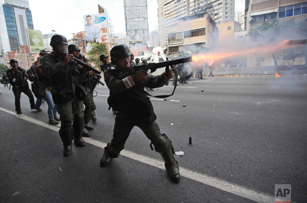 A Bolivarian National Guard officer fires teargas toward demonstrators during a protest in Caracas, Venezuela, Thursday, April 6, 2017. The South American country has seen near-daily protests since the Supreme Court issued a ruling nullifying congress last week. The court pulled that decision back after it came under heavy criticism, but opposition leaders said the attempt to invalidate a branch of power revealed the administration's true dictatorial nature.(AP Photo/Ariana Cubillos)