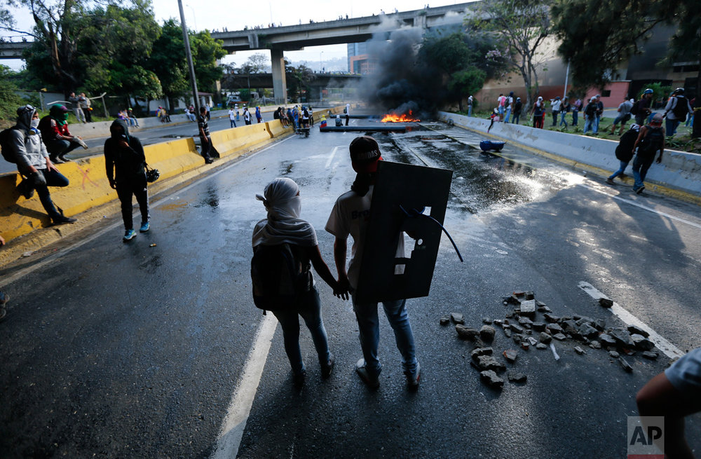 A couple hold hands at a road block set by anti-government protesters in Caracas, Venezuela, Monday, April 24, 2017. Thousands of protesters shut down the capital city's main highway to express their disgust with the socialist administration of President Nicolas Maduro. Protesters in at least a dozen other cities also staged sit-ins as the protest movement is entering its fourth week. (AP Photo/Ariana Cubillos)