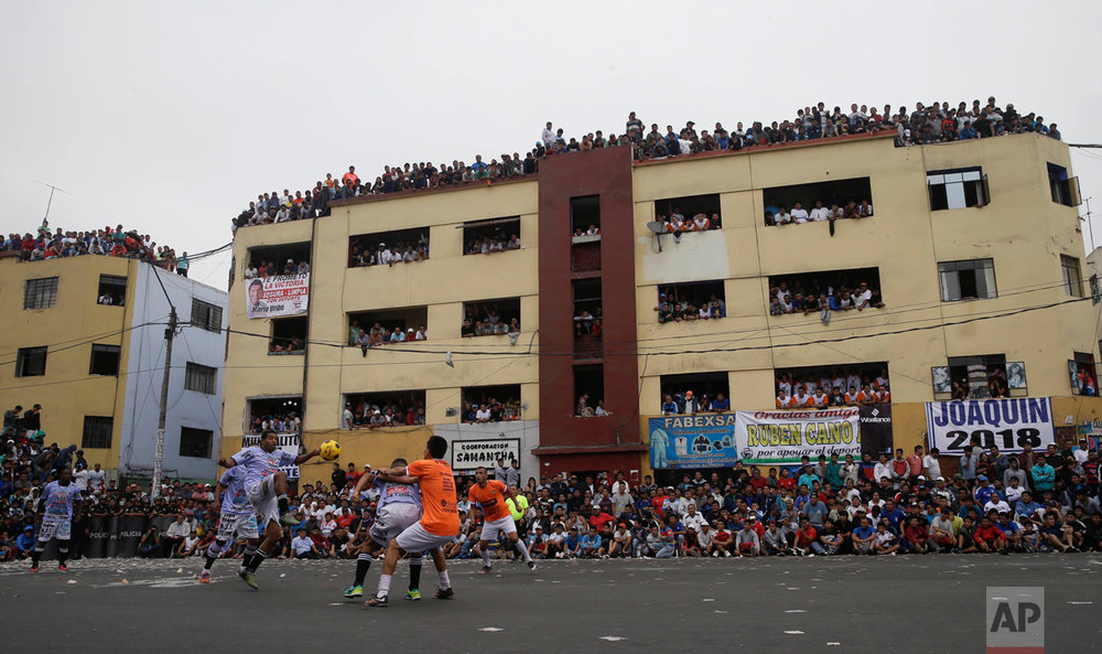 "In this Monday, May 1, 2017 photo, residents crowd the balconies of an apartment building to watch soccer teams ""La Polvora,"" (Gun Powder) and ""Los Chatarreros"" (The Scrappers) play a semi-final game at the Little World Cup Porvenir street soccer championship in Lima, Peru. Residents pay about $2 dollars for a balcony view of the annual ritual. (AP Photo/Martin Mejia)"