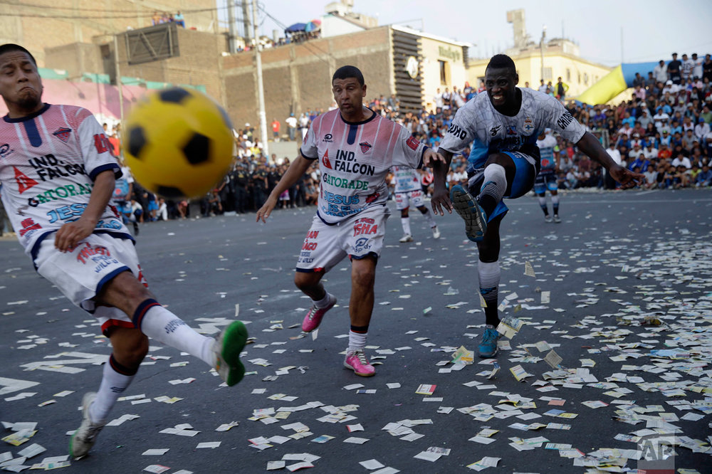 "In this Monday, May 1, 2017 photo, teams ""Purito Barrios Altos"" and ""Ají San Cosme"" play the final game at the Little World Cup of Provenir street soccer championship in Lima, Peru. The tournament has been a big focus for Peruvian fans for a while, because the country's national team hasn't qualified to play in international soccer's World Cup since 1982. (AP Photo/Martin Mejia)"