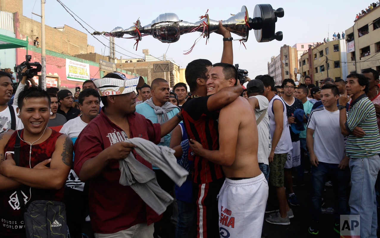 "In this Monday, May 1, 2017 photo, a fan of the ""Purito Barrios Altos"" soccer team holds high his team's trophy as he hugs a player after the Little World Cup of Provenir street soccer championship in Lima, Peru. The team clenched the championship after a day of 30 back-to-back games. (AP Photo/Martin Mejia)"