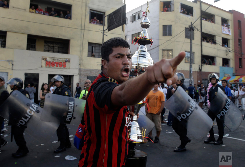 "In this Monday, May 1, 2017 photo, a fan of the ""Purito Barrios Altos"" soccer team yells at rival fans who don't agree with the referee's decision as he runs with his team's trophy after the Little World Cup of Provenir street soccer championship in Lima, Peru. All 56 teams bring their fans to defend each goal, even if it comes to blows, so about 50 anti-riot police line the pitch. (AP Photo/Martin Mejia)"