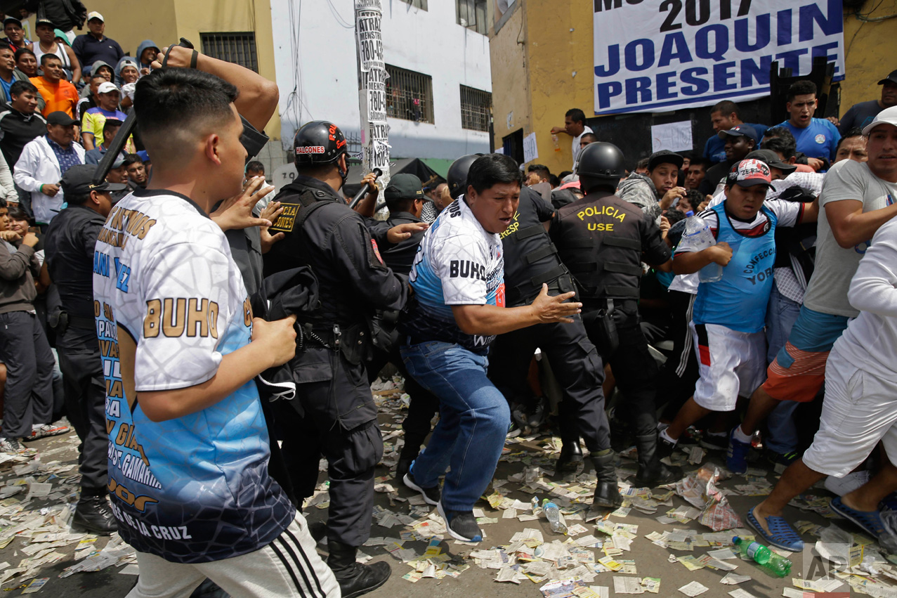 In this Monday, May 1, 2017 photo, soccer fans force themselves past police during an interval between games at the Little World Cup of Provenir street soccer championship in Lima, Peru. Dozens of teams bring their fans to defend each goal, even if it comes to blows, so anti-riot police line the pitch. (AP Photo/Martin Mejia)