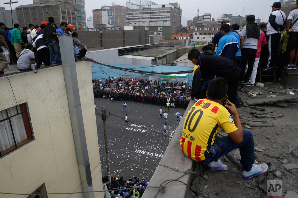 In this May 1, 2017 photo, people watch the Little World Cup of Provenir street soccer championship from an apartment roof top, for which they pay about $2 dollars, in Lima, Peru. To score good seats, people camp out the night before, lining the road where the games have packed the streets every May 1 for a half century. (AP Photo/Martin Mejia)