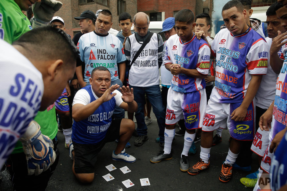 In this Monday, May 1, 2017 photo, coach Nestor Paredes huddles with his players before their semi-final game at the Little World Cup Porvenir street soccer championship in Lima, Peru. The wining team takes home this year's trophy, a $2,500 cash prize and 12 pairs of soccer cleats. (AP Photo/Martin Mejia)