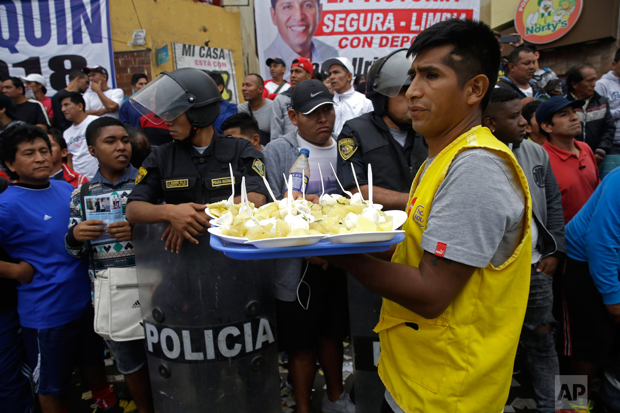 In this Monday, May 1, 2017, a food vendor works the crowd during a break at the Little World Cup of Provenir street soccer championship in Lima, Peru. His tray is filled with plates of baked potatoes, boiled eggs and a spicy cream. (AP Photo/Martin Mejia)