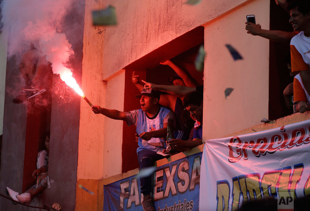 In this Monday, May 1, 2017 photo, a soccer fan lights a flare from an apartment building balcony overlooking the Little World Cup Porvenir street soccer championship in Lima, Peru. The working-class neighborhood ritual in El Porvenir began in the 1950s as a challenge to the Manuel Odria military dictatorship when playing in the streets was forbidden. (AP Photo/Martin Mejia)