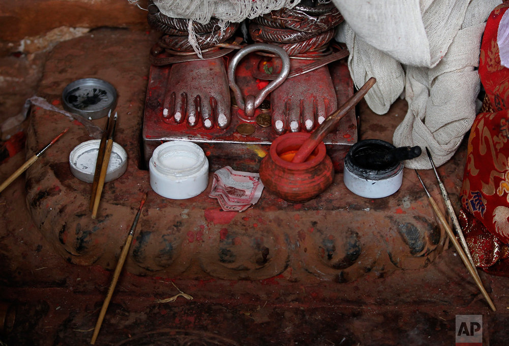 In this April 22, 2017, photo, paint and brushes sit at the feet of the statue of Rato Machindranath as it is painted in time for the Rato Machindranath festival, in Machindra Bahal in Lalitpur, Nepal. Legend says that around the 7th century there was massive drought in the Kathmandu valley. It was believed that the arrival of the red deity would end the drought and bring back the rainfall. Hence then King Narendra Dev along with a priest and farmer travelled to what is now the Assam state in India and brought back Karunamaya, the god of compassion. It is popularly now known as Rato Machindranath. (AP Photo/Niranjan Shrestha)