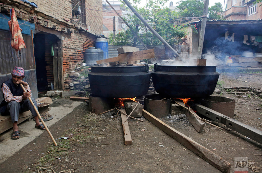 In this April 20, 2017, photo, a man soaks cane in hot water cauldrons to make it flexible for use in the construction of the Rato Machindranath Chariot in Lalitpur, Nepal. The wooden chariot is built to appease the gods in hopes of being blessed with good rainfall followed by a bountiful harvest. The Rato Machindra festival that centers on the chariot in the capital Kathmandu, preludes the monsoon season in Nepal where majority of the population still depend on farming for livelihood. (AP Photo/Niranjan Shrestha)