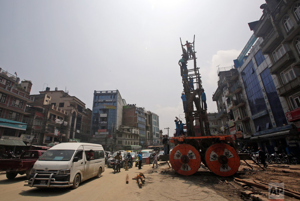 In this April 21, 2017, photo, members of the Barahi community construct the 15-meter (48-foot) tall Rato Machindranath Chariot in Lalitpur, Nepal. The wooden chariot is built to appease the gods in hopes of being blessed with a good rainfall followed by a bountiful harvest. The Barahis are responsible for repairing the giant wheels, carving the base and erecting the tower of logs for the chariot. (AP Photo/Niranjan Shrestha)