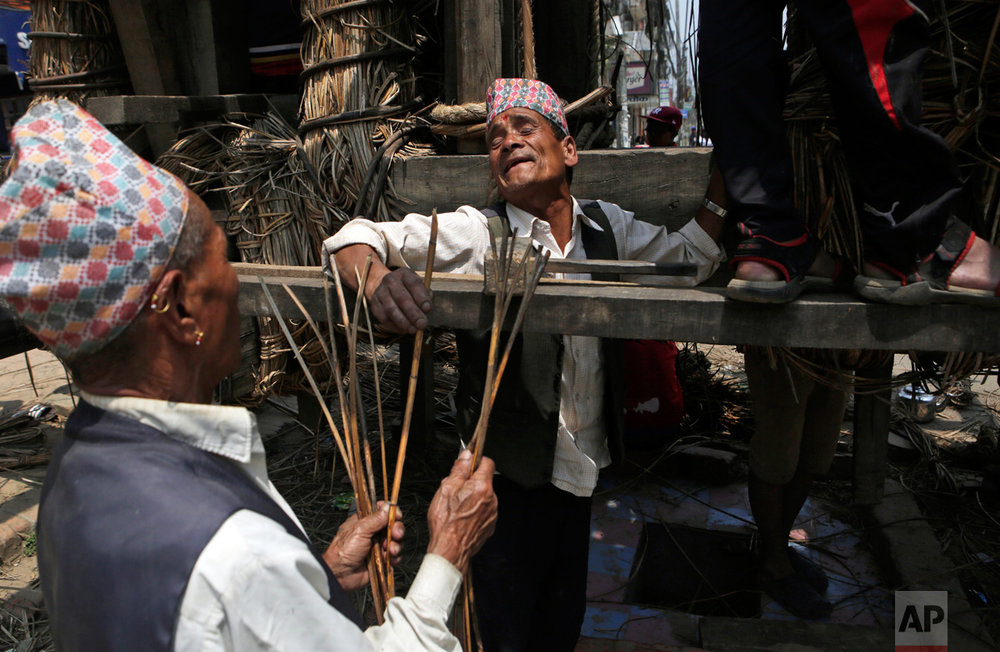 In this April 18, 2017, photo, members of the Yanwal community use strips of cane to construct the Rato Machindranath Chariot in Lalitpur, Nepal. The wooden chariot is built to appease the gods in hopes of being blessed with a good rainfall followed by a bountiful harvest. The chariot built every year is 15-meter (48-foot) tall and based on a chassis that is only wide as a small truck. The Yanwals have the task of tying the tower of logs together with truck-loads of cane fibers. (AP Photo/Niranjan Shrestha)
