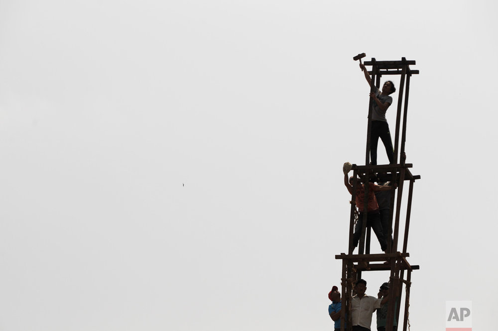 In this April 21, 2017, photo, members of the Barahi community skillfully construct the 15-meter (48-foot) tall Rato Machindranath Chariot without safety harnesses in Lalitpur, Nepal. If a chariot falls during the annual race which takes place in Kathmandu, it is seen as a bad omen for the Himalayan nation. The last chariot crash was just weeks after the then king seized absolute power and in the months that followed Nepal was in turmoil with political unrest, escalating communist insurgency and a dwindling economy. This year workers hope for a clean race and good times ahead for the country. (AP Photo/Niranjan Shrestha)