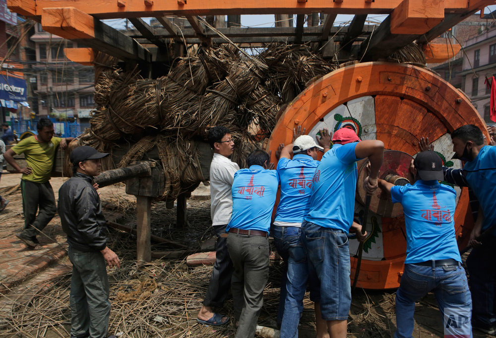 In this April 21, 2017 photo, members of the Barahi community assemble the Rato Machindranath Chariot in Lalitpur, Nepal. The Barahis are responsible for repairing the giant wheels, carving the base and erecting the tower of logs for the chariot. The wooden chariot is built to appease the gods in hopes of being blessed with a good rainfall followed by a bountiful harvest. (AP Photo/Niranjan Shrestha)