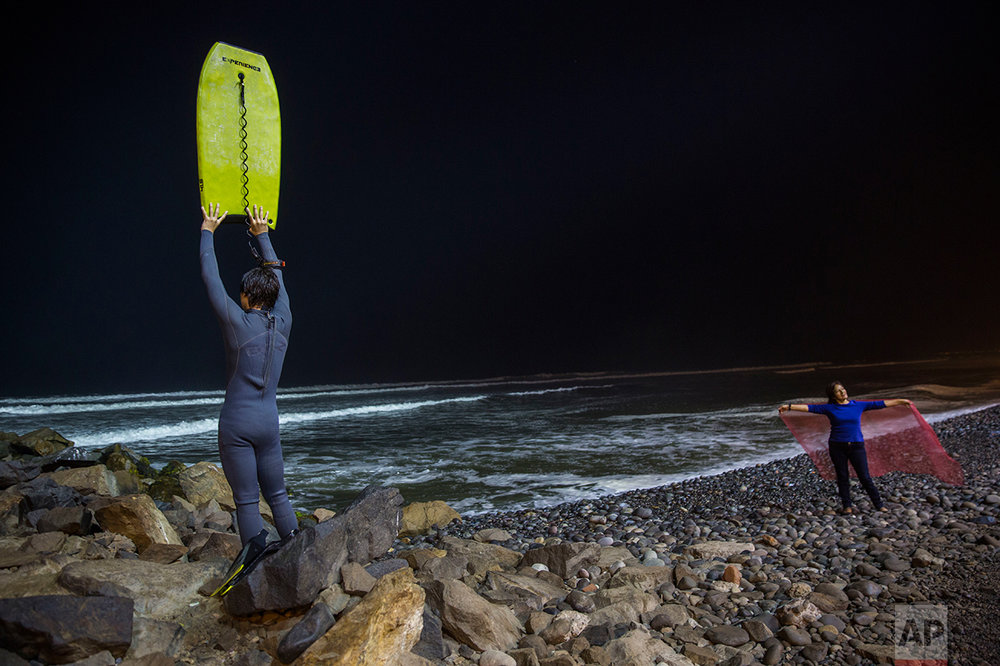 In this April 21, 2017 photo, Renato de Negri, 15, lifts his boogie board to signal to a fellow surfer in Pacific Ocean waters that he has returned to shore, at La Pampilla beach, in Lima, Peru. Pampilla beach does not attract sharks, unlike some beaches in the United States and Australia. The greatest danger faced by night surfers is that they can crash into each other, blinded by the powerful floodlights. (AP Photo/Rodrigo Abd)