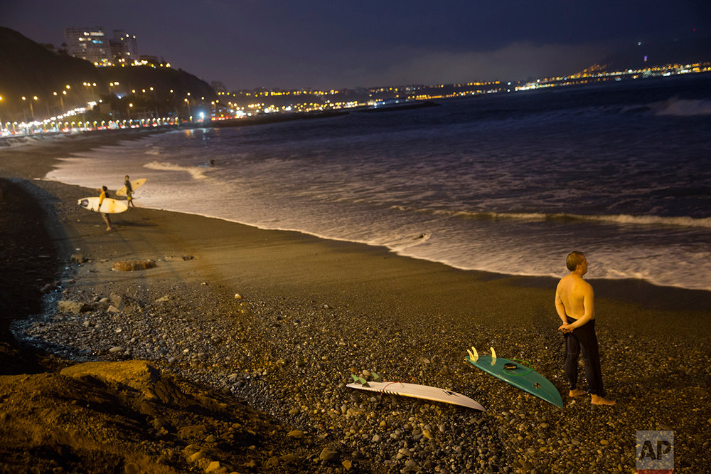 In this April 21, 2017 photo, a man looks out at the Pacific Ocean from the shore at La Pampilla beach in Lima, Peru. Pampilla is the second beach in Latin America that is set up for night surfing. (AP Photo/Rodrigo Abd)