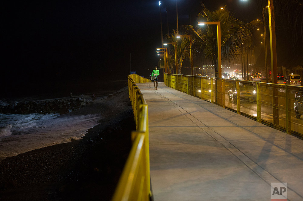 In this March 1, 2017 photo, a surfer walks along the promenade that lines La Pampilla beach in Lima, Peru. The Andean country has decked out Pampilla with four 1,000-watt light like those used in soccer stadiums, providing enough illumination to surf after nightfall. (AP Photo/Rodrigo Abd)