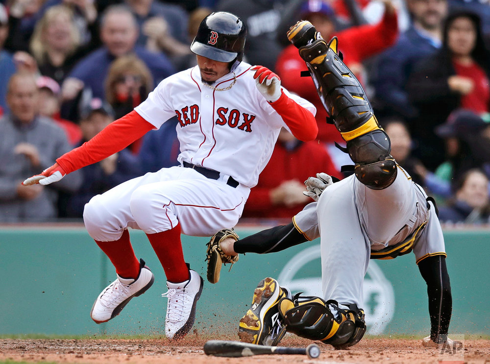 Pittsburgh Pirates catcher Chris Stewart, right, tags out Boston Red Sox's Mookie Betts while trying to score on a hit by Hanley Ramirez during the eighth inning of a baseball game at Fenway Park in Boston, Thursday, April 13, 2017. (AP Photo/Charles Krupa)