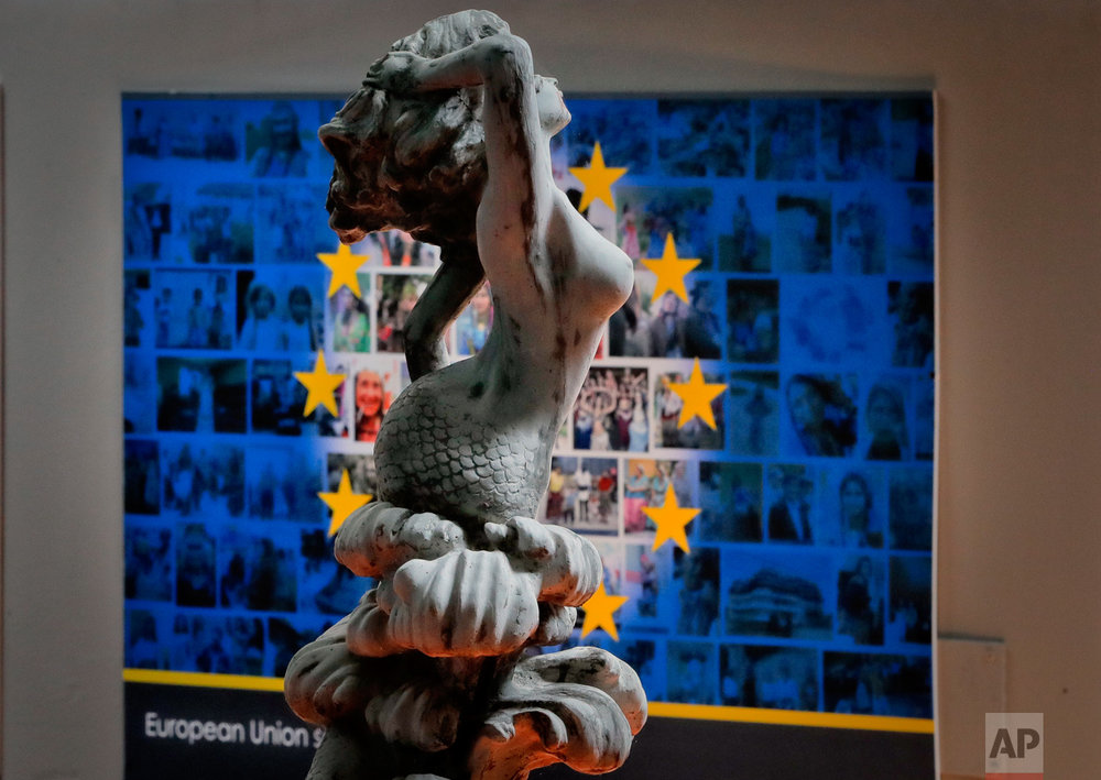 In this Thursday, May 4, 2017, photo a plaster statue is backdropped by an interpretation of the European Union flag at the newly opened Bucharest Kitsch Museum, in Bucharest, Romania. (AP Photo/Vadim Ghirda)