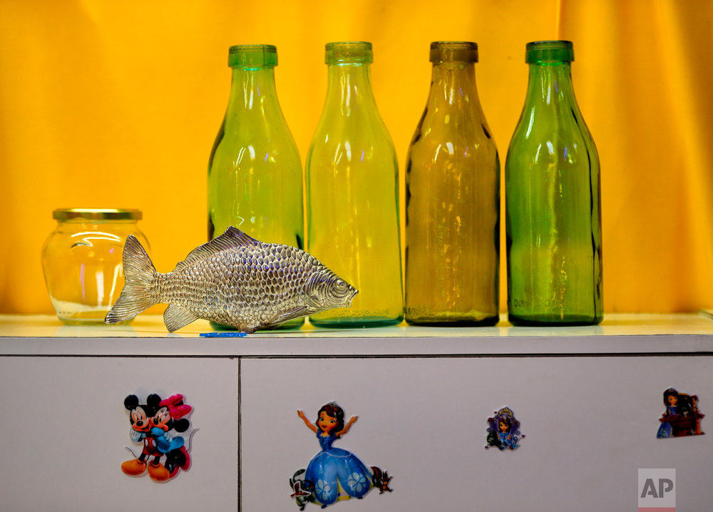 In this Thursday, May 4, 2017, photo Communist era milk bottles are on display along with a metal fish at the newly opened Bucharest Kitsch Museum, in Bucharest, Romania. (AP Photo/Vadim Ghirda)