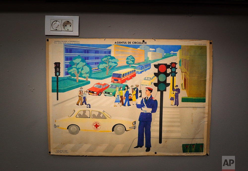 In this Thursday, May 4, 2017, photo a Communist education ministry poster depicting a traffic policeman is on display at the newly opened Bucharest Kitsch Museum, in Bucharest, Romania. (AP Photo/Vadim Ghirda)