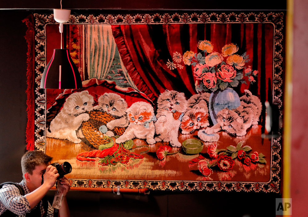 In this Thursday, May 4, 2017, photo a news photographer works inside the newly opened Bucharest Kitsch Museum, in Bucharest, Romania. (AP Photo/Vadim Ghirda)