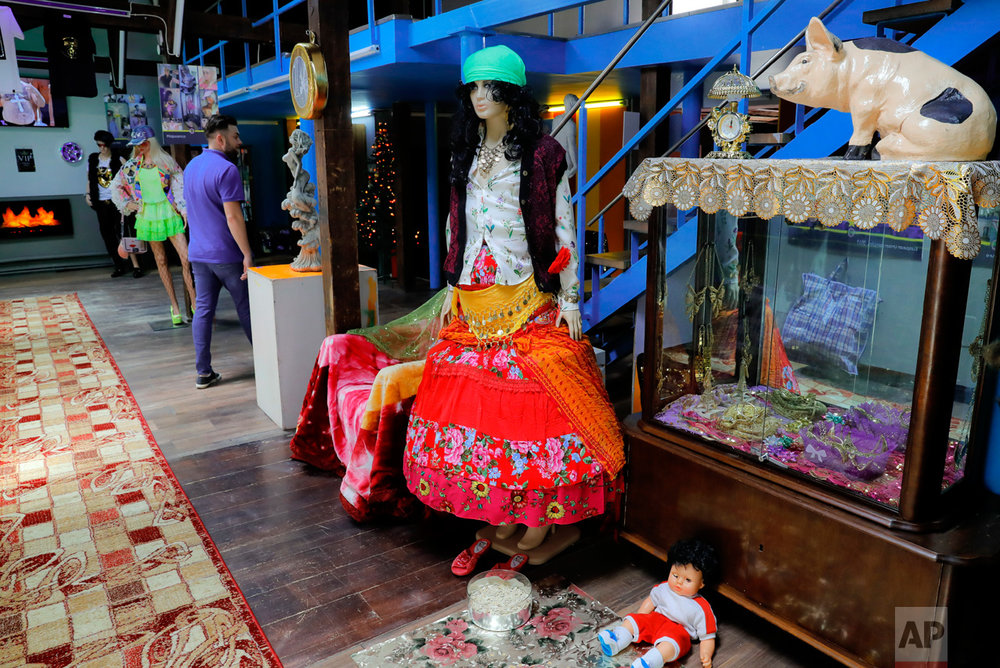In this Thursday, May 4, 2017, photo a man walks by exhibits in the Gypsy kitsch section at the newly opened Bucharest Kitsch Museum, in Bucharest, Romania. (AP Photo/Vadim Ghirda)