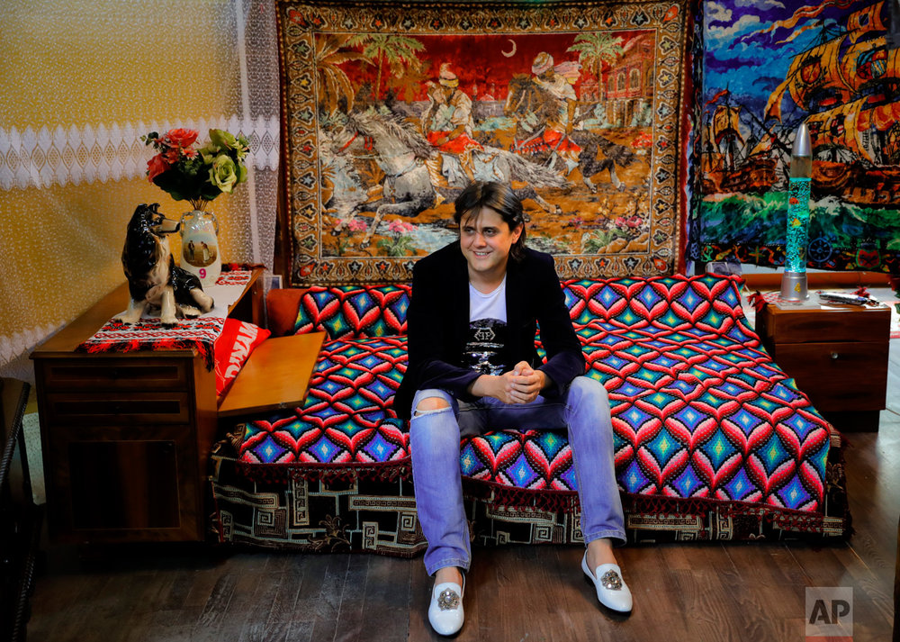 In this Thursday, May 4, 2017, photo museum owner Cristian Lica poses at the newly opened Bucharest Kitsch Museum, in Bucharest, Romania. The Kitsch Museum opens for visitors on Friday, May 5, 2017. (AP Photo/Vadim Ghirda)