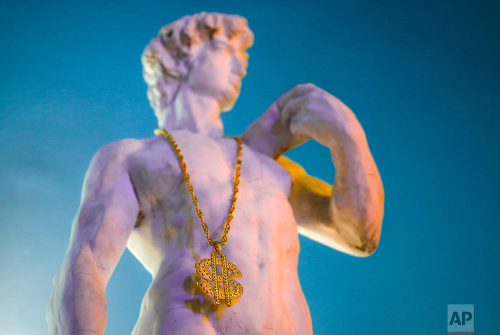 In this Thursday, May 4, 2017, photo a replica of Michelangelo's world-famous statue of David wearing a gaudy gilt necklace with a large US dollar ($) pendant, stands at the entrance to the newly opened Bucharest Kitsch Museum, in Bucharest, Romania. (AP Photo/Vadim Ghirda)