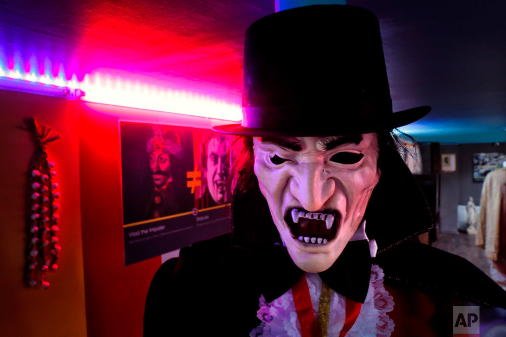 In this Thursday, May 4, 2017, photo a mannequin depicting Dracula is backdropped by a poster attempting to differentiate Bram Stoker's character from Romanian medieval ruler Vlad the Impaler, seen at left, at the newly opened Bucharest Kitsch Museum, in Bucharest, Romania. (AP Photo/Vadim Ghirda)