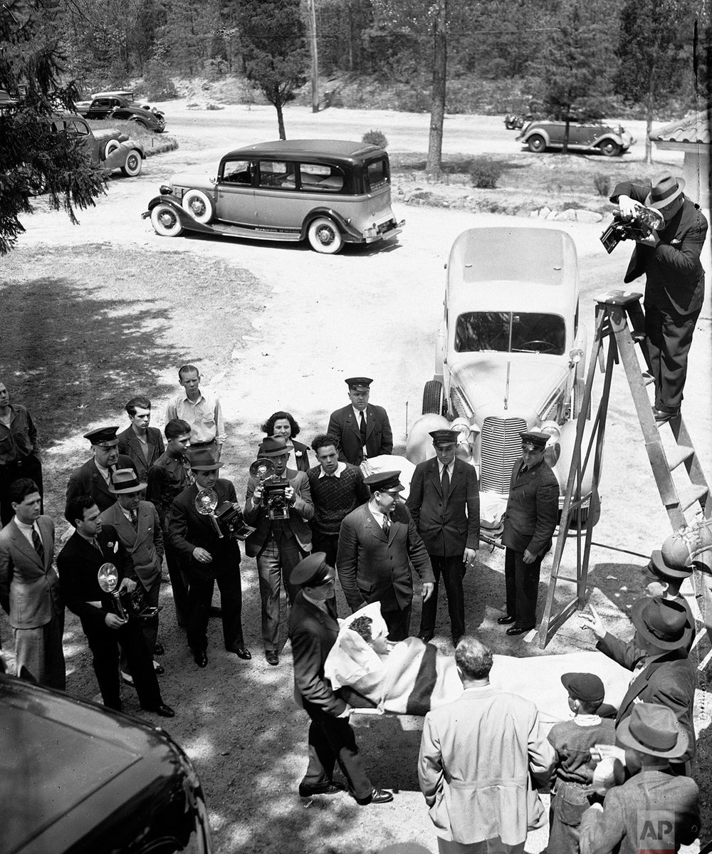In this May 7, 1937 photo, news photographers take pictures of an unidentified survivor of the German dirigible Hindenburg disaster the previous day, as survivors are transferred from Paul Kimball Hospital in Lakewood, N.J., to other area hospitals. (AP Photo)