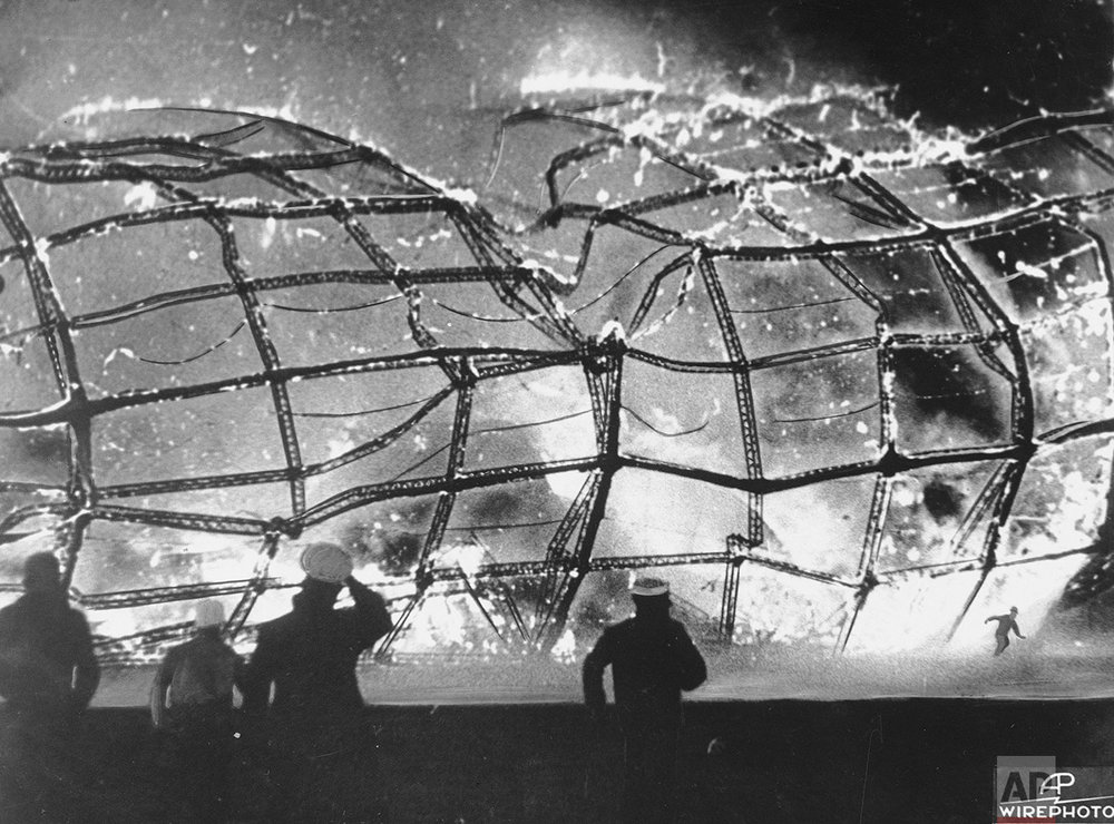 The blazing inferno that was the German airship Hindenburg is reduced to ruins as a survivor, lower right hand corner, runs to safety, May 6, 1937, after it exploded on mooring at Lakehurst Naval Air Station in New Jersey.  Rescuers, left and center, rush forward to pull other passenger and crew away from the fiery wreckage. (AP Photo)