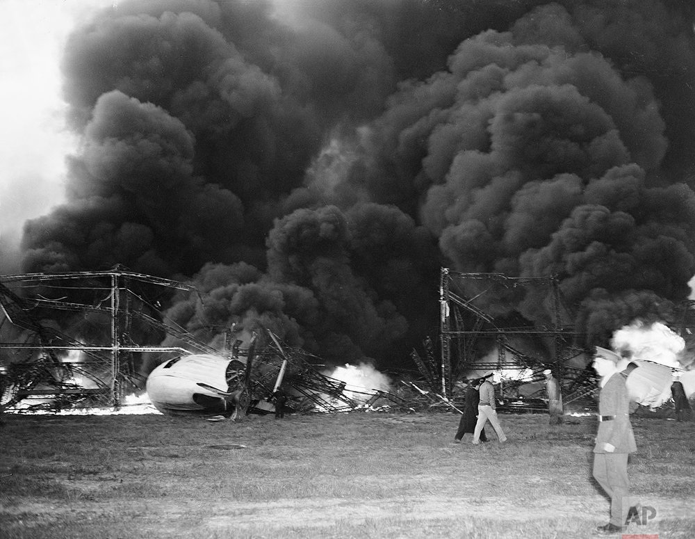 Black smoke rises from the skeleton of the burning Hindenburg airship at Lakehurst, N.J., May 6, 1937. The German-built zeppelin caught fire and exploded mid-air as it was landing after its transatlantic voyage, carrying 97 passengers and crew.  Thirty-five people on board and one ground crew member were killed.  (AP Photo/Murray Becker)