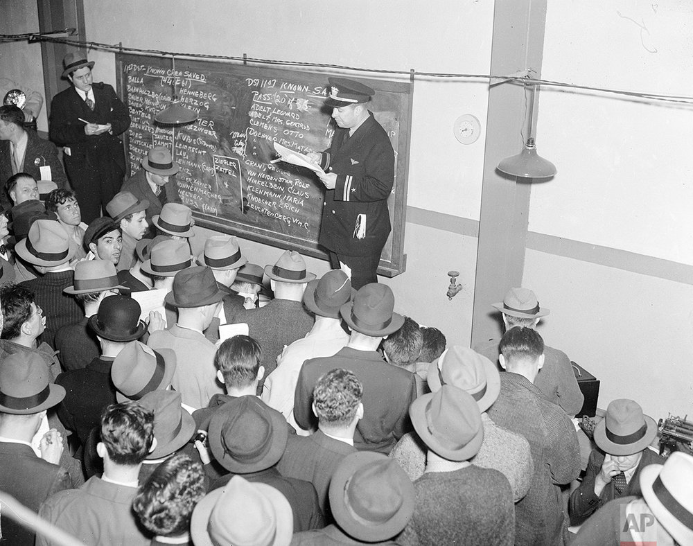 Relatives and friends of persons listed as missing in the Hindenburg disaster check the bulletin board on which the names of survivors are being added in Lakehurst, N.J., May 7, 1937.  The German-built zeppelin, carrying 97 passengers and crew, burst into flames in mid-air as it was landing after its transatlantic voyage May 6.  Thirty-five people on board and one ground crew member were killed.  (AP Photo)