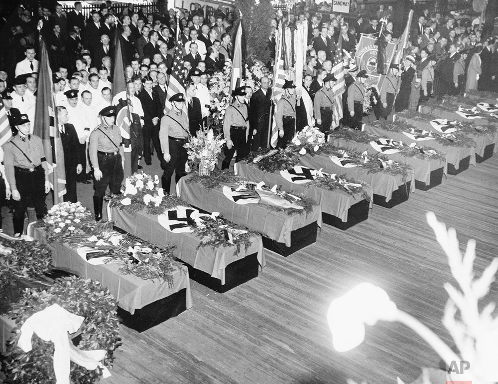 Funeral services for the 28 Germans who lost their lives in the Hindenburg disaster May 6 are held on the Hamburg-American pier in New York City, May 11, 1937.  The swastika-draped caskets will be placed on board the Hamburg for their return to Europe.  About 10,000 members of German organizations line the pier.  (AP Photo/Anthony Camerano)