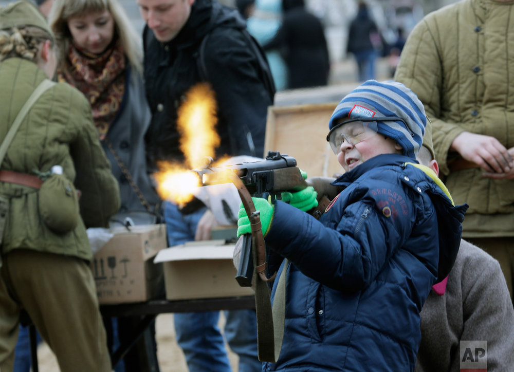 A boy shoots a World War II-era machine gun armed with blanks at a weapon exhibition during a military show in St. Petersburg, Russia, on Sunday, April 30, 2017. (AP Photo/Dmitri Lovetsky)