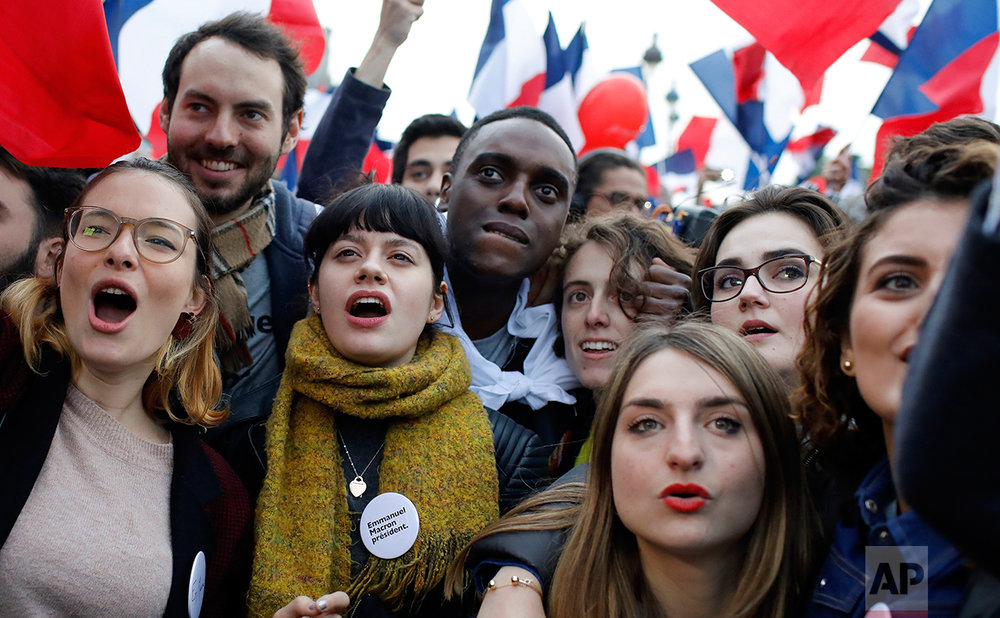 Supporters of French independent centrist presidential candidate, Emmanuel Macron wait for the results outside the Louvre museum in Paris, France, Sunday, May 7, 2017. (AP Photo/Laurent Cipriani)