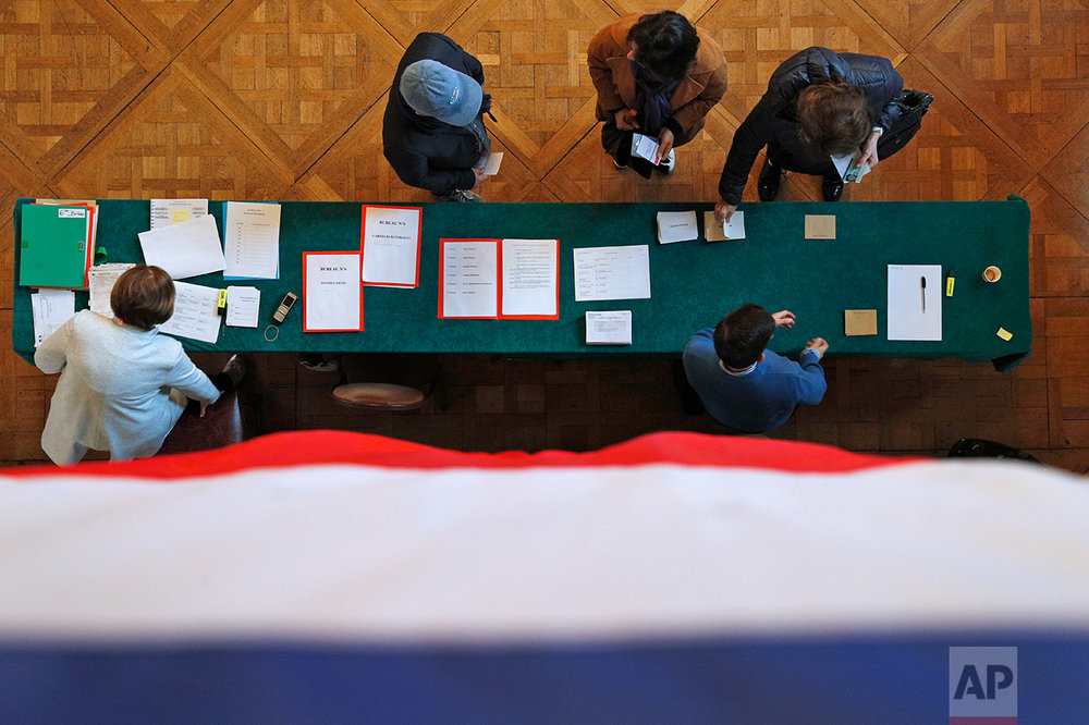 The French flag hangs from a balustrade as voters cast their ballots in the presidential runoff election between Emmanuel Macron and Marine Le Pen, in Le Touquet, France, Sunday, May 7, 2017.  (AP Photo/Christophe Ena)