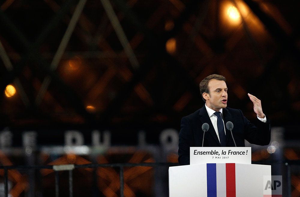 "French President-elect Emmanuel Macron gestures as he speaks during a victory celebration outside the Louvre museum in Paris, France, Sunday, May 7, 2017. Speaking to thousands of supporters from the Louvre Museum's courtyard, Macron said that France is facing an ""immense task"" to rebuild European unity, fix the economy and ensure security against extremist threats. (AP Photo/Thibault Camus)"