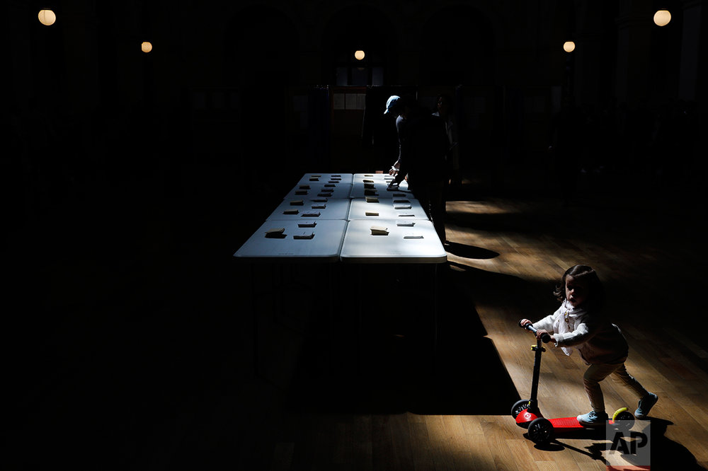 A girl rides a scooter as a man picks up ballots for the first round of the French presidential election in Lyon, central France, Sunday April 23, 2017. (AP Photo/Laurent Cipriani)