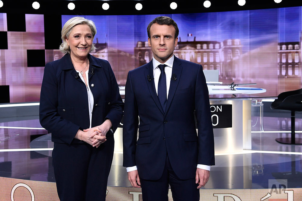 French presidential election candidate for the far-right Front National party, Marine Le Pen, 2nd left, and French presidential election candidate for the En Marche ! movement, Emmanuel Macron, right, pose prior to the start of a live broadcast face-to-face televised debate in La Plaine-Saint-Denis, north of Paris, France, Wednesday, May 3, 2017 as part of the second round election campaign. (Eric Feferberg/Pool Photo via AP)