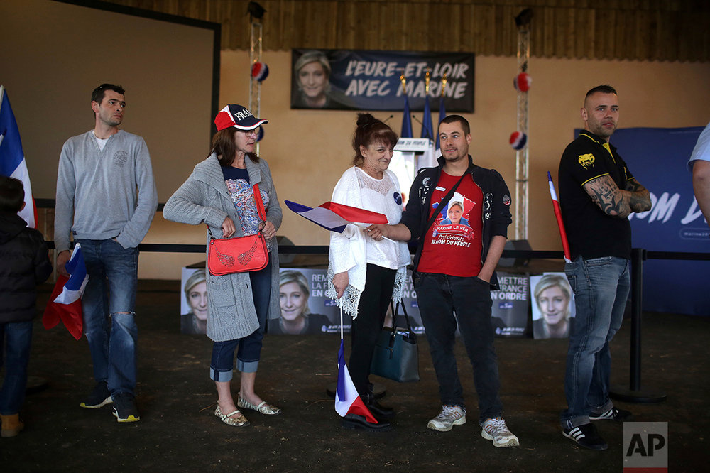 Supporters of Far-right candidate for the presidential election Marine Le Pen, wait prior to a meeting in La Bazoche Gouet, central France, Monday, April 3, 2017. A self-described patriot, Le Pen hopes to extract France from the European Union and do away with France's membership in the shared euro currency. (AP Photo/Thibault Camus)