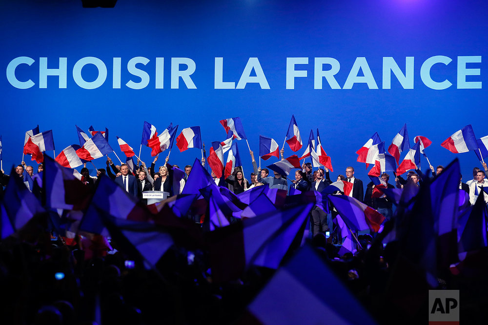French conservative candidate from the first-round election Nicolas Dupont-Aignan, left, and french far-right presidential candidate Marine Le Pen cheer their supporters at the end of their meeting, Monday May 1, 2017, in Villepinte, outside Paris. (AP Photo/Francois Mori)