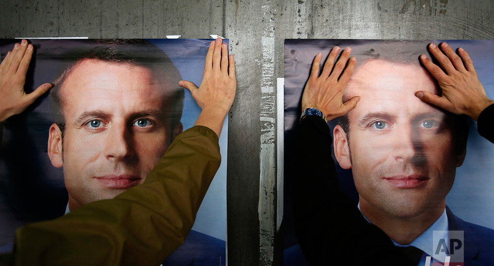 A supporter of French centrist presidential candidate Emmanuel Macron puts up a campaign poster, in Lille, northern France, Tuesday, May 2, 2017.  (AP Photo/Michel Spingler)