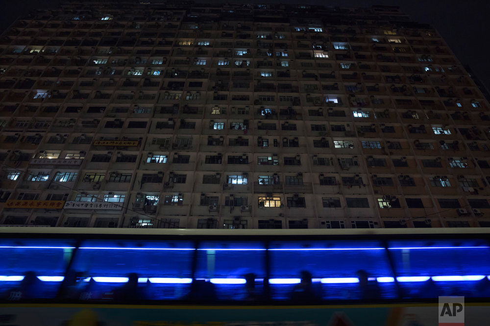 "In this Tuesday, April 25, 2017 photo, a bus drives past a residential and commercial building where the ""coffin homes"" are located in Hong Kong. There's a dark side to the property boom in wealthy Hong Kong, where hundreds of thousands of people priced out of the market must live in partitioned apartments, ""coffin homes"" and other inadequate housing. As a new leader for the territory prepares to take office, housing unaffordability remains one of the Asian financial center's biggest social problems. (AP Photo/Kin Cheung)"