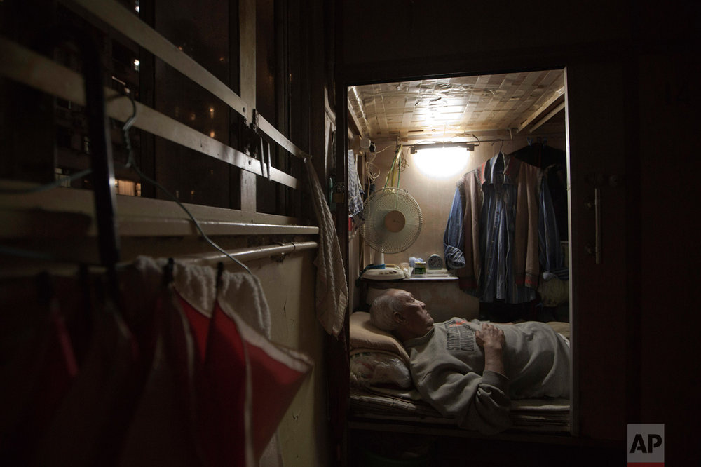 "In this Thursday, March 28, 2017 photo, Tse Chu, a retired waiter, sleeps in his ""coffin home"" in Hong Kong. In wealthy Hong Kong, there's a dark side to a housing boom, with hundreds of thousands of people forced to live in partitioned shoebox apartments, ""coffin homes"" and other ""inadequate housing. (AP Photo/Kin Cheung)"