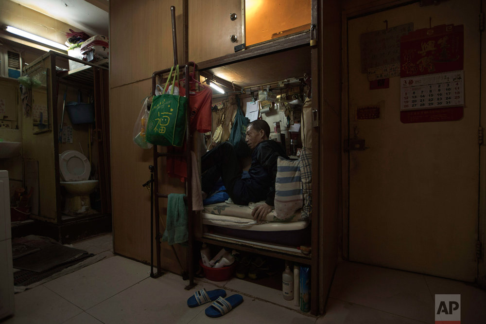 "In this Thursday, March 28, 2017 photo, Wong Tat-ming, 63, sits in his ""coffin home"" which is next to a set of grimy toilets in Hong Kong as he pays HK$2,400 ($310) a month for a compartment measuring three feet by six feet. It's crammed with all his meager possessions, including a sleeping bag, small color TV and electric fan. (AP Photo/Kin Cheung)"