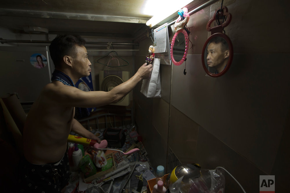 "In this Thursday, May 4, 2017 photo, a resident who only gave his surname Sin, 55, tidies up the bed in his ""coffin home"" in Hong Kong. In wealthy Hong Kong, there's a dark side to a housing boom, with hundreds of thousands of people forced to live in partitioned shoebox apartments, ""coffin homes"" and other ""inadequate housing. (AP Photo/Kin Cheung)"